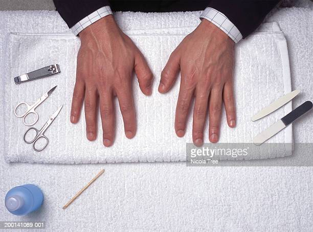 manicure equipment around man's hands on towel, overhead view - nail scissors stock pictures, royalty-free photos & images