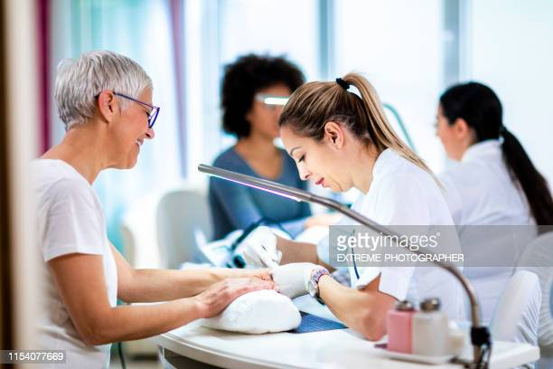 manicure specialist tidying up an elderly woman's fingernails using cuticle removal tools in a manicure center - nail salon stock pictures, royalty-free photos & images
