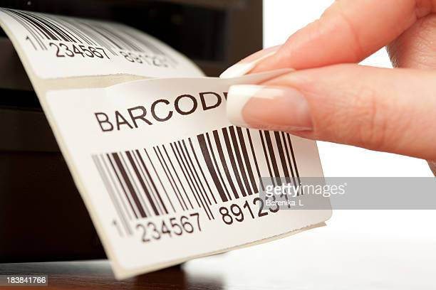 Manicured nails on woman's hand peeling barcode sticker