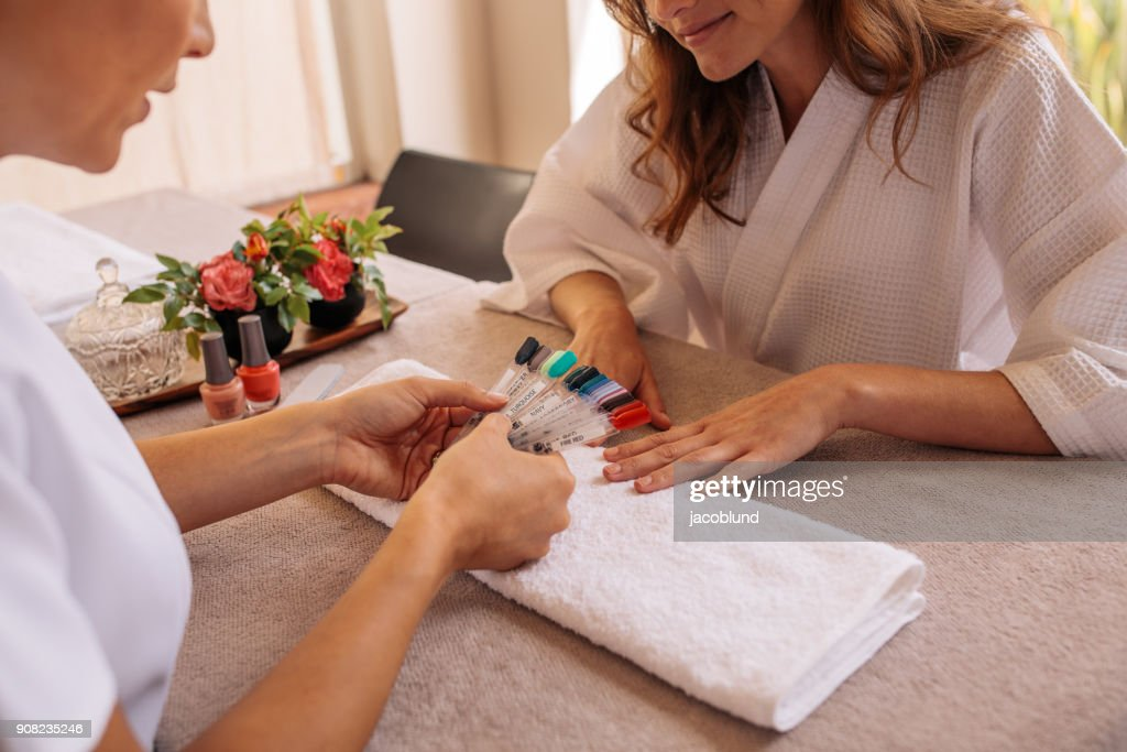 Manicurist displaying samples of nail patterns to client : Stock Photo