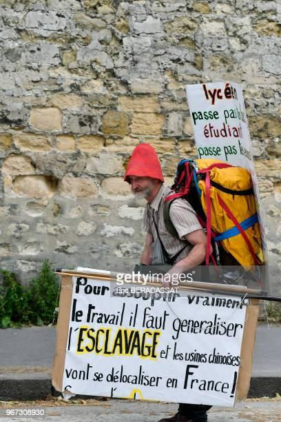 Manifestant avec des affiches 'Pour assouplir vraiment le travail il faut généraliser l'esclavage et les usines chinoises vont se délocaliser en...