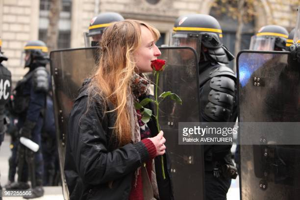 Manifestante avec une rose et police anti émeute lors de la manifestation pour defendre le climat et rappeler l'etat d'urgence climatique place de la...