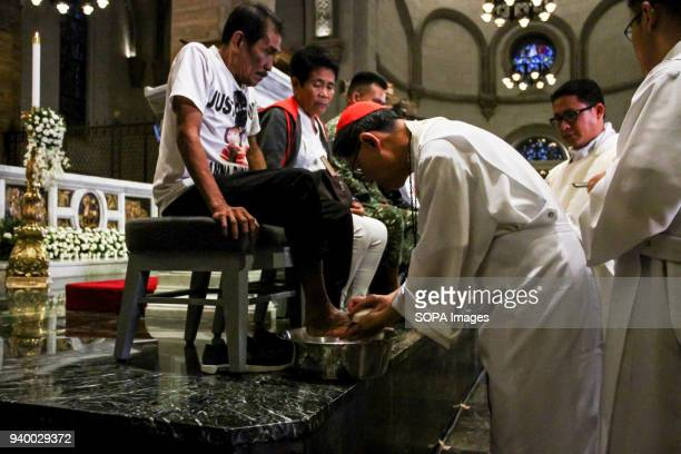 Manila Archbishop Antonio Cardinal Tagle washes the foot of the father of Joanna Demafelis a Filipina worker in Kuwait killed by her employer...