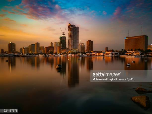 manila city with reflection and pastel color sky - lorena day stock pictures, royalty-free photos & images