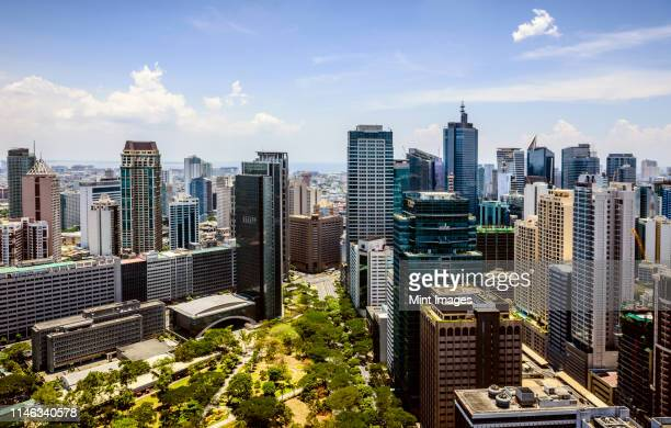 manila cityscape under blue sky, philippines - makati stock photos and pictures