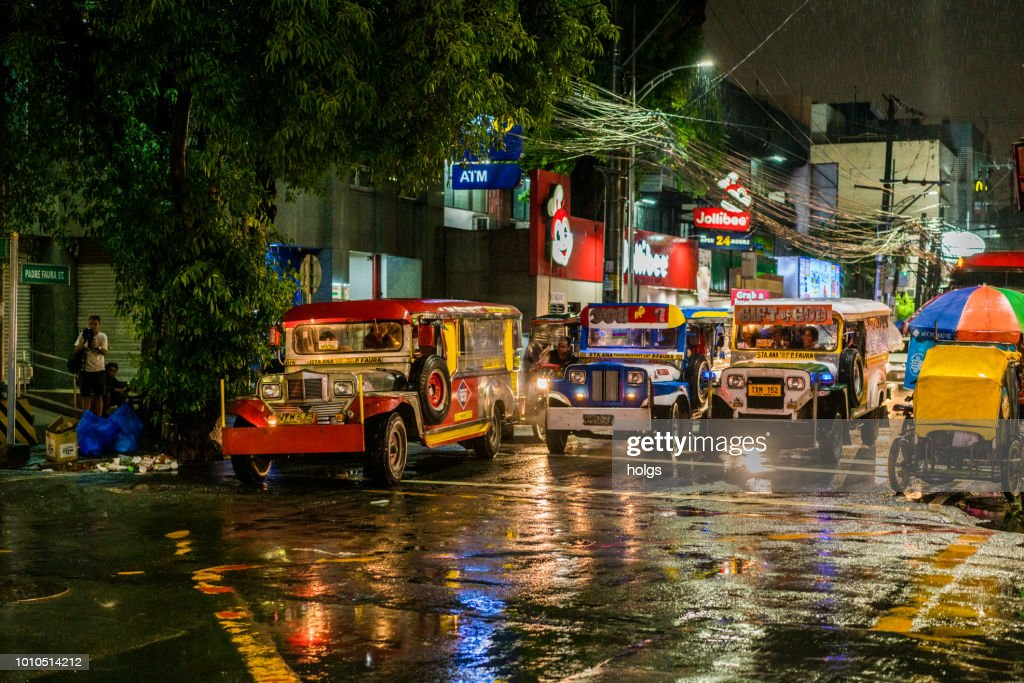 Manila Malate area by night city street jeepneys pedicabs on the street on a rainy night : Stock Photo