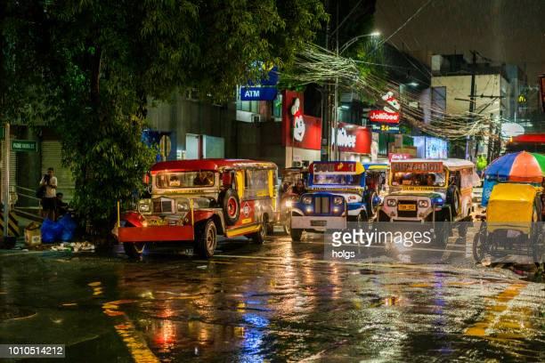 manila-malate bereich durch nacht stadt straße jeepneys fahrradrikscha auf der straße an einem regnerischen abend - metro manila stock-fotos und bilder