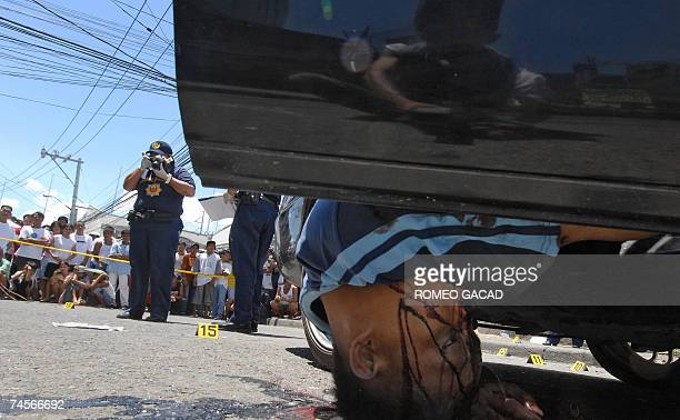 A body of suspected bank robber hangs from a bullet riddled car while police investigators work on the scene following a shootout with policemen near...