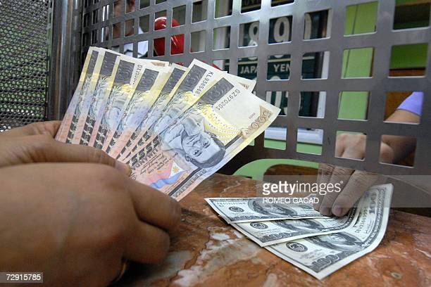 A customer counts her Philippine peso after changing her US dollars at a moneychanger in Manila 03 January 2007 The peso closed stronger at 48880 to...