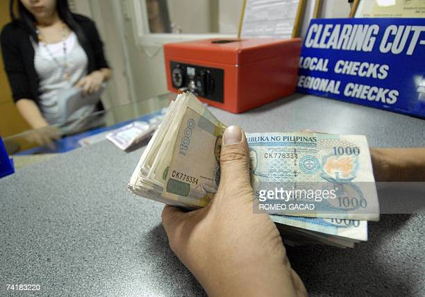 A customer holds Philippine peso notes during a bank transaction in Manila 18 May 2007 as the country's currency hit a six year high of 4660 against...