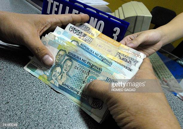 A Customer Holds Philippine Peso Notes During Bank Transaction In Manila 18 May 2007 As