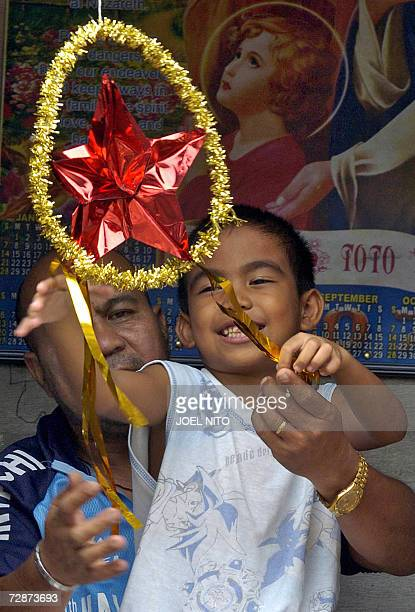 A father and his young son enjoy a light moment together playing with a lantern at their home beside a railroad track in Manila on the eve of...