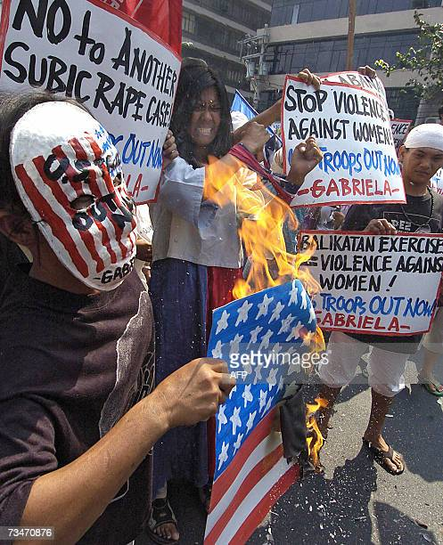 A group of antiUS demonstrators burn a mock US flag as they try to march to the US embassy in Manila 19 February 2007 to protest against the joint...