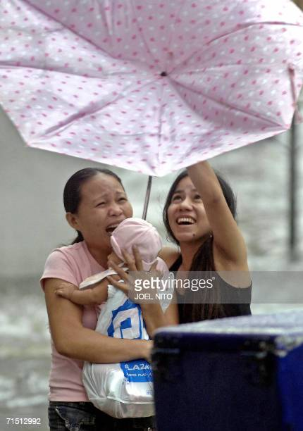A woman carrying a baby placed in plastic bag to protect him from strong rain reacts as wind pulls their umbrella while crossing a flooded street in...