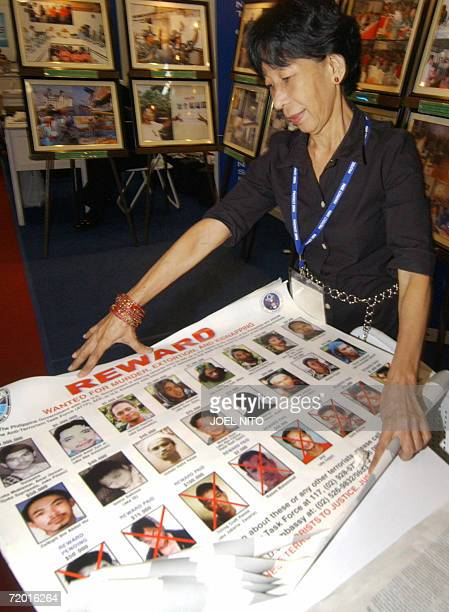 An exhibitor prepares posters carrying portraits of wanted Filipino terrorist belonging to the alQaeda linked Abu Sayyaf group and the two...