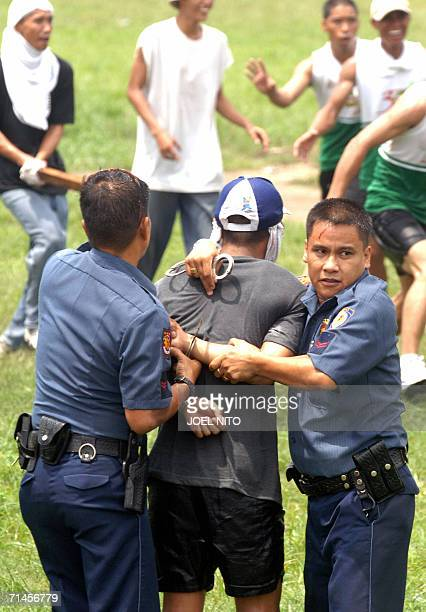 Antiriot policemen handcuff a mock protester during a drill in Manila 16 july 2006 as they prepare for the expected protests on July 24 when...