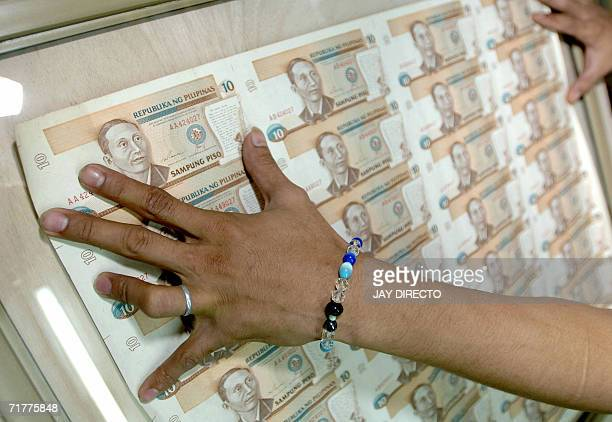 Craftsman Christian Lazo sets into a frame a sheet of uncut commemorative 10peso bills in Manila 03 September 2006 The peso closed at 50735 to the US...
