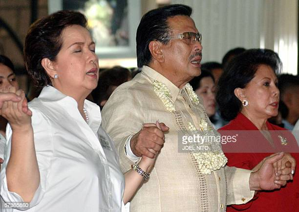 Deposed Philippine president Joseph Estrada join hands in prayer with his wife Luisa Ejercito and Susan Roces widow of opposition presidential...