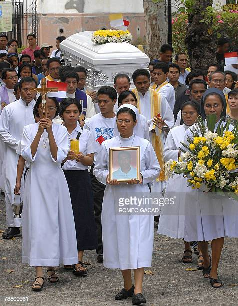 Filipino and Indonesian nuns and priests carry the coffin bearing the remains of Indonesian Roman Catholic priest Franciskus Madhu on arrival at the...