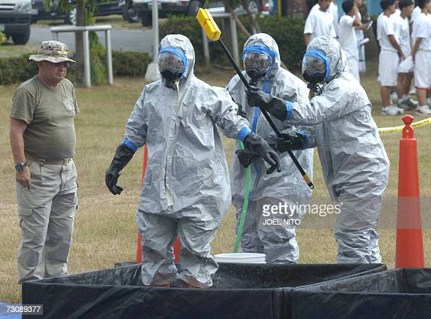Filipino participants in chemical suits are watched by a US instructor as they decontaminate colleagues as they check for radiation during a exercise...