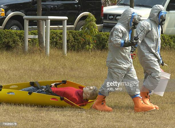 Filipino participants wearing chemical suits pull a mock victim during a exercise on Radiological dispersal devices at a public safety college in...