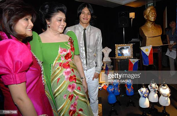 Former first lady Imelda Marcos accompanied by daughter Congresswoman Imee Marcos and grandson Borgy Manotoc a fashion model pose beside the bust of...