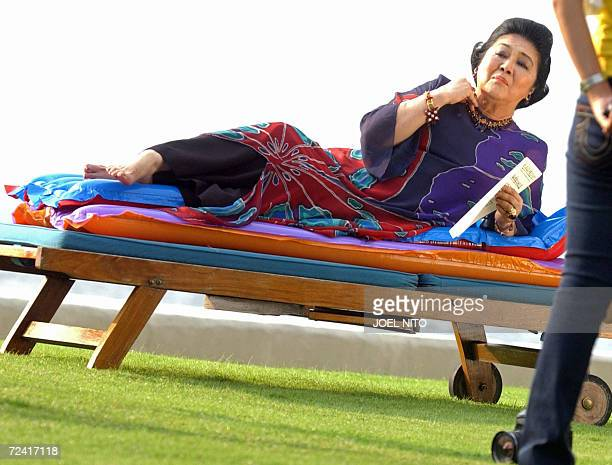 Former Philippines first lady Imelda Marcos arranges her necklace for a photo shoot beside the bayside pool of a top hotel in Manila 06 November 2006...