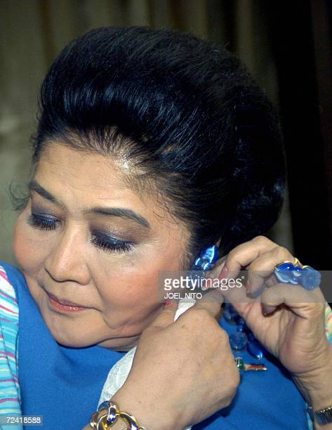 Former Philippines first lady Imelda Marcos adjusts her earrings as she takes part in a photo shoot beside the bayside pool of a top hotel in Manila...