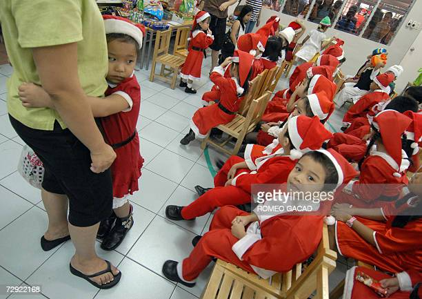 Four year old Mikaela Jose clings to her mother Cristine while her classmates wear Santa Claus costume as they prepare for the Christmas program at a...