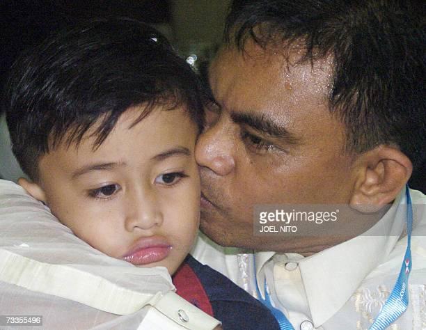 One of 26 Filipino seamen whose vessel was seized last month by gunmen in Nigeria's oil region motorman Edgardo Ellera kisses his son Kent karl after...