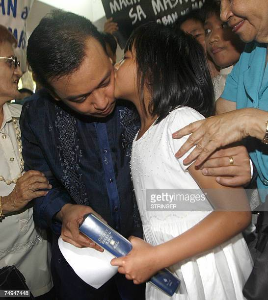 Opposition candidate and now a newlyelected Senator Lt Senior Grade Antonio Trillanes receives a kiss from his daughter Estelle after taking his oath...
