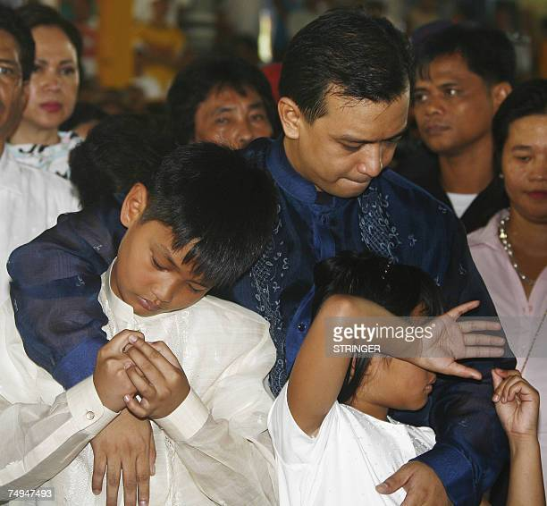 Opposition candidate and now a newlyelected senator Lt Senior Grade Antonio Trillanes hugs his children Francis 9 and Estelle before taking his oath...