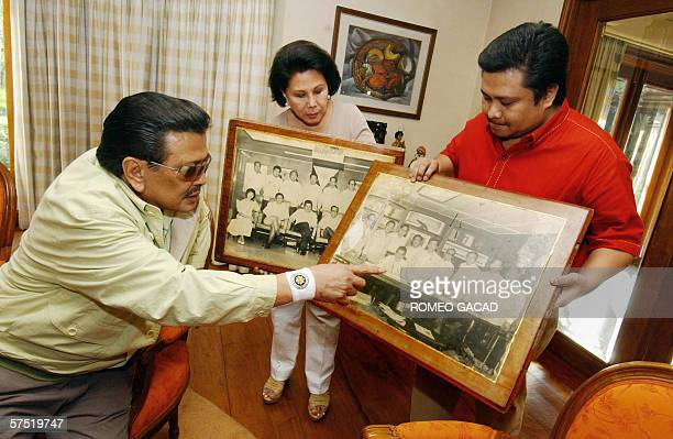 Ousted Philippine president Joseph Estrada looks at his memorabilia pictures shown by his son Senator Jinggoy Estrada and his wife Senator Luisa...