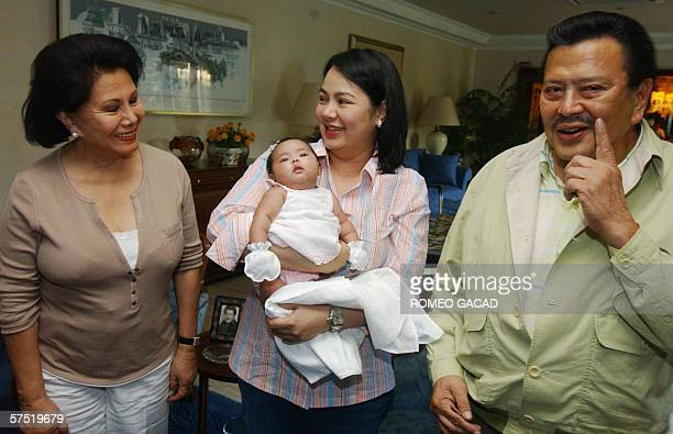 Ousted Philippine president Joseph Estrada gestures next to his daughterinlaw Precy Estrada and grand daughter Jill Estrada joined by his wife...