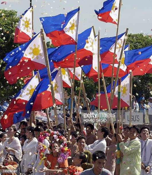 Performers wave the Philippine flag under a shower of confetti during the 109th Philippine Independence Day celebration at the Rizal park grandstand...