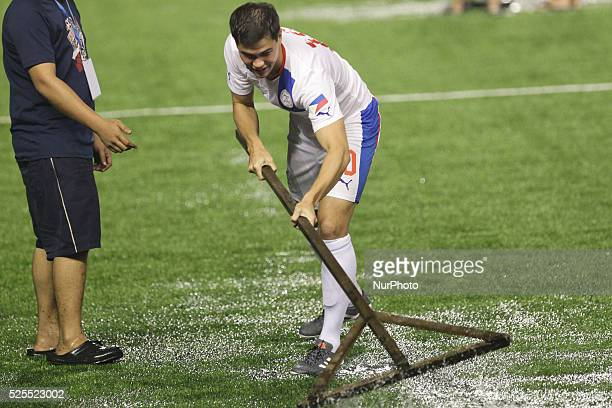 Manila Philippines Phil Younghusband of the Philippines swipes water off the field after rain delayed the game against ChineseTaipei for almost an...