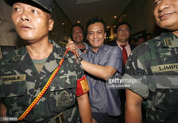Philippine senatorial candidate and detained former Philippine navy officer Antonio Trillanes is escorted by his marine escorts moments after leaving...