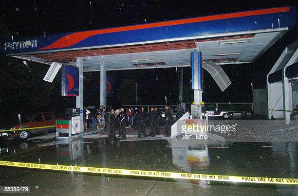 Police and firefighers stand at a gasoline station damaged by an ammunitions dump explosion at the Diaw police camp in suburban Manila 13 September...