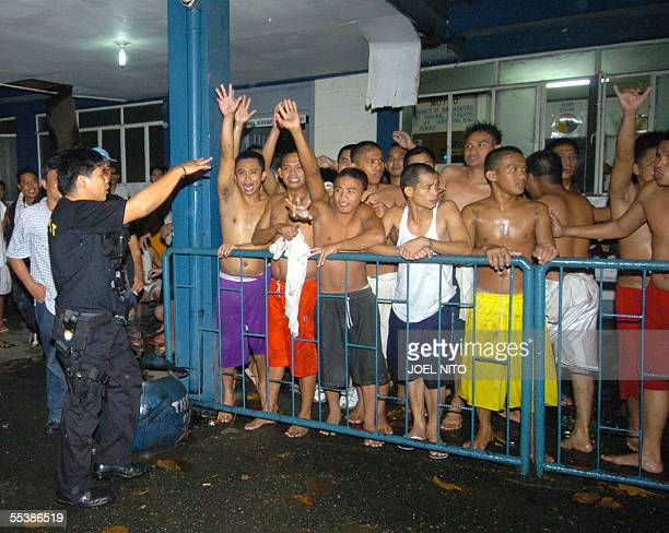 Police calms prisoners of the Diwa camp before transfer to another camp after an ammunition dump exploded nearby 13 September 2005 in Manila No...