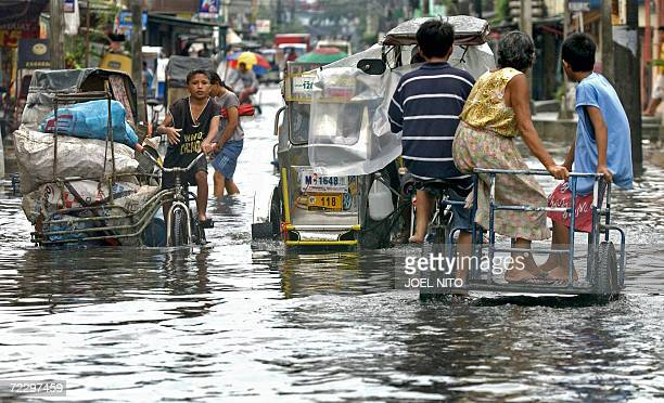 Residents make their way through flooded streets in Malabon suburban Manila 30 October 2006 after powerful Typhoon Cimaron lashed the northern...