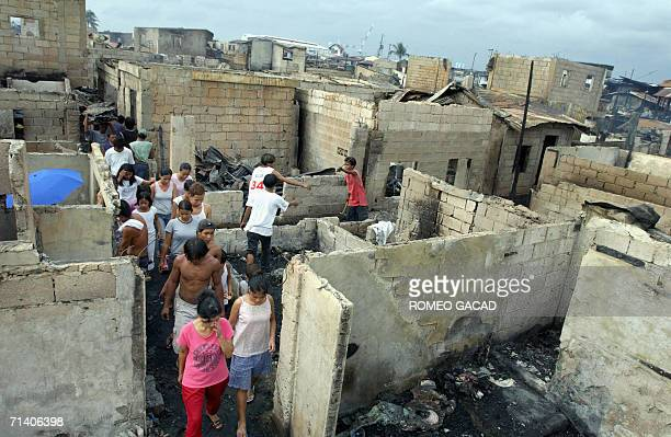 Residents search their burned houses for salvage items following a predawn fire in Malabon suburban Manila 10 July 2006 Some 1500 families were left...