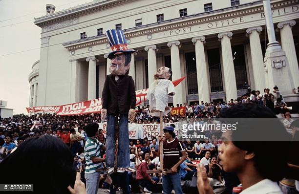 Manila, Philippines: Students parade the effigies of President Reagan and President Marcos before they burn in front of the Manila post office.
