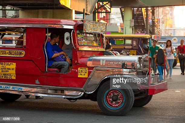 manila, philippines2: red jeepney in traffic - jeepney stock pictures, royalty-free photos & images
