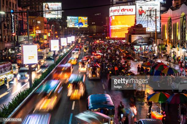 manila qiapo  area by night busy street cars and market vendors on the street and people buying - manila philippines stock pictures, royalty-free photos & images