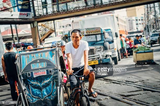 Manila-Straßenszene mit Rikscha-Fahrer