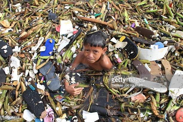 Manila Tondo New Smokey Mountain Ulingan Charcoal Factory Philippines garbage rubbish sea water bath dirt smelly boy kid child swim