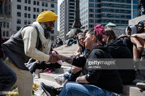 Maninder Singh Walia, a leader of the Sikh community, shakes hands with family members of the deceased at Monument Circle in Indianapolis, Indiana on...