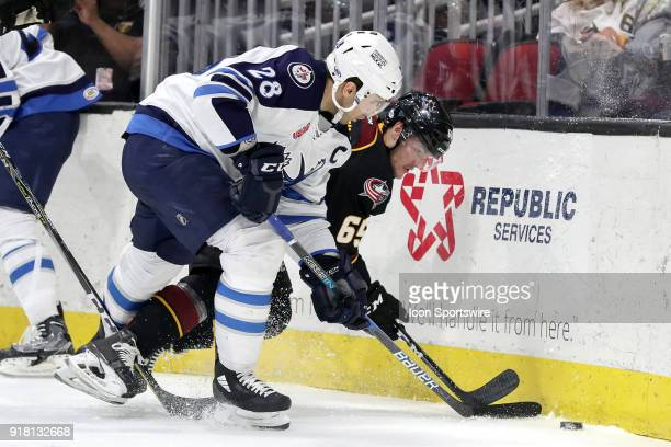 Manitoba Moose center Patrice Cormier battles Cleveland Monsters defenceman Garret Cockerill for the puck during the third period of the American...