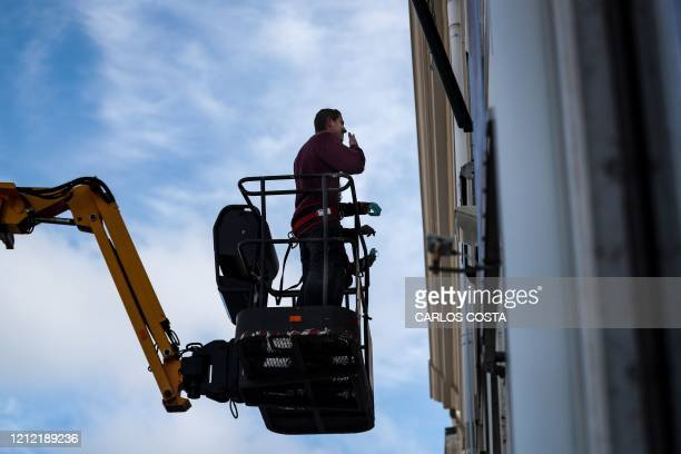 A manlift crane elevates relatives of elderly residents of Santo Antonio retirement house in Figueira da Foz to allow them meeting but keeping their...