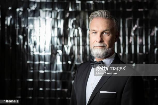 mann im anzug mit grauen haaren und bart - cool, smart und seriös - 蝶ネクタイ ストックフォトと画像